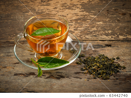 A cup of tea and tea leaf on a background 63442740