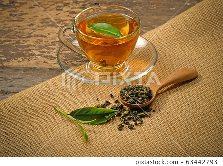 A cup of tea and tea leaf on a background 63442793