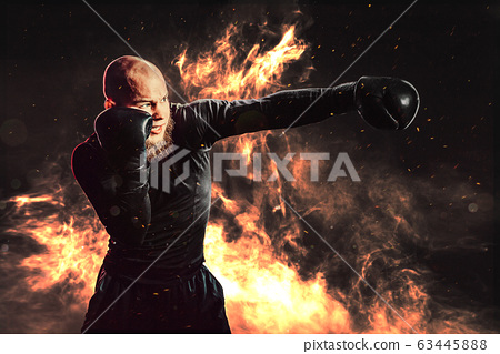 Sportsman boxer training, hitting direct hit on background with fire. Boxing sport concept 63445888