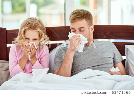 Sick family. Father and daughter suffering from flu or cold and wiping noses while lying in bed together at home. Virus disease 63471360