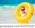Adorable little girl having fun on the beach 63474587