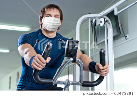 fitness girl in gym in medical mask 63475891