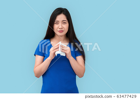 Freestyle. Chinese woman standing isolated on grey with tissue sneezing unhappy 63477429
