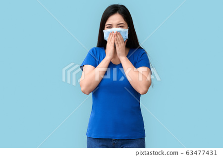 Coronavirus Concept. Chinese woman in medical mask standing isolated on grey coughing unhappy 63477431