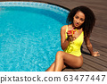 Summer Vacation. Young african woman by the pool sitting drinking cocktail posing to camera confident 63477447