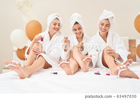 Friends in towels and bathrobes doing pedicure. 63497830