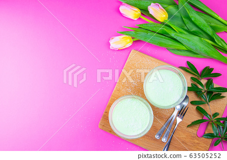 Mint lemon yogurt with kiwi in salad bowls on a wooden board along with tulips on a pink background 63505252