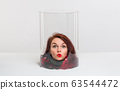 The head of a woman in a scarf under a transparent cap. Conceptually. self- isolation from coronavirus 63544472
