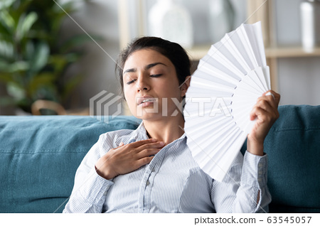 Overheated Indian woman waving paper fan, feeling unwell 63545057