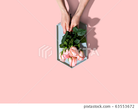 Woman holding pink roses overhead view 63553672