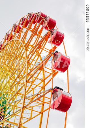 Ferris wheel with cloudy sky in Kobe, Japan 63555890