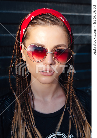 Fashion portrait of young hipster woman with bandana and sunglasses. Hairstyle small braids 63563663