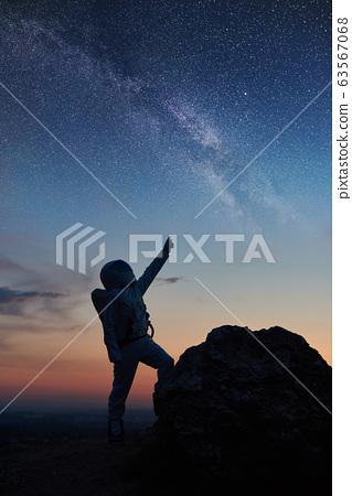 Astronaut standing under beautiful night sky. 63567068
