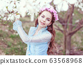 Cute girl stands near the magnolia tree. 63568968