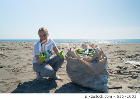 woman picks up trash from the beach in trash bags 63571003