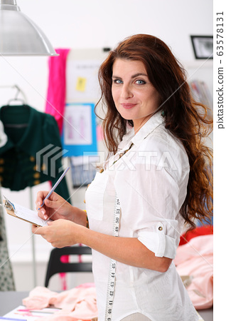 Tailor writes measurements in pad by color pencil 63578131