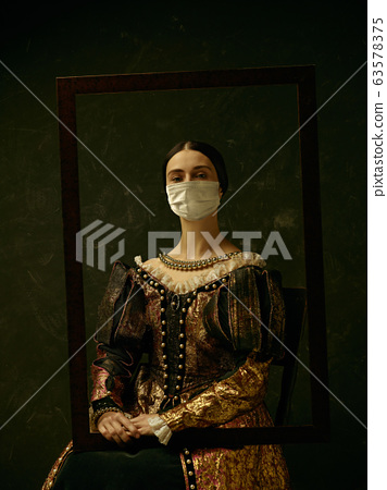 Medieval young woman as a duchess wearing protective mask against coronavirus spread 63578375