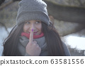 Joyful Caucasian girl touching nose and looking aside. Portrait of happy cheerful young woman having fun on river bank outdoors. Leisure, joy, lifestyle, happiness. 63581556