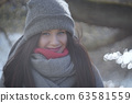 Portrait of grey-eyed young woman smiling at camera. Close-up of charming brunette Caucasian girl posing on river bank in park. Lifestyle, nature, leisure. 63581559