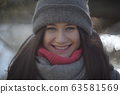 Close-up portrait of happy brunette girl with toothy smile looking at camera. Joyful young woman with grey eyes posing outdoors. Leisure, joy, happiness, lifestyle. 63581569