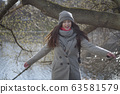 Portrait of cheerful young woman at the background of water in park or forest. Positive Caucasian girl having fun outdoors on sunny autumn day. Leisure, happiness, lifestyle. 63581579