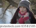 Thoughtful brunette girl looking away outdoors. Portrait of gorgeous young Caucasian woman spending sunny autumn day on river bank. Nature, lifestyle, leisure. 63581585