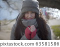 Charming young Caucasian woman holding hands together on sunny autumn day. Portrait of brunette girl in warm clothes looking at camera outdoors. 63581586