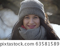 Portrait of smiling young Caucasian woman looking at camera. Close-up of positive girl in autumn hat enjoying sunny day outdoors. Joy, lifestyle, leisure. 63581589