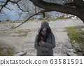Portrait of young cute girl standing outdoors and thinking. Young Caucasian woman in warm coat and hat spending sunny autumn day in park. 63581591