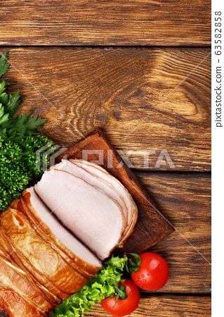 Delicious smoked ham on a wooden rustic board with 63582858