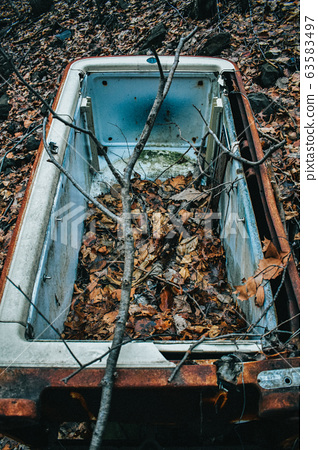 A Vertical Shot of an Abandoned Fridge 63583497