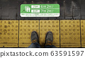 Feet stand on the yellow line beside the train 63591597