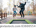 Mom and her daughter jumping together on trampoline in autumn park 63600554