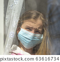 Sick girl look at the window with longing on the street . 63616734