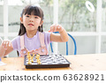happy beautiful girl playing chess on wood table floor at home. 63628921