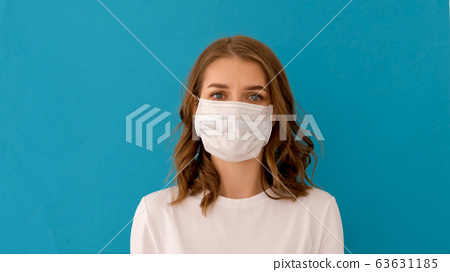 Woman putting on surgical mask for corona virus prevention 63631185