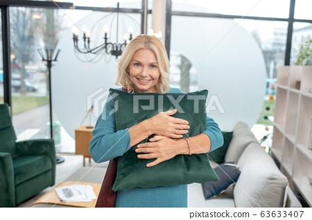 Beautiful woman hugging a green decorative pillow in a store. 63633407