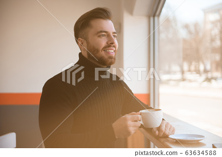 Attractive successful young businessman drinking coffee sitting at cafe table. 63634588