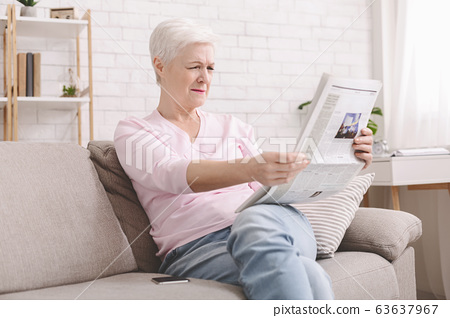 Senior lady squinting and holding newspaper far from eyes 63637967