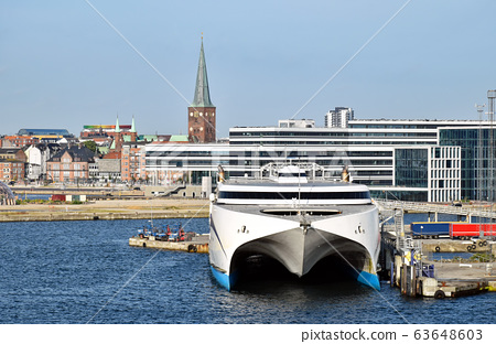 A high-speed ferry has moored in the harbor of Aarhus (Denmark). In the background modern and historic buildings can be seen. 63648603