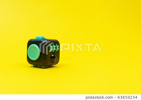 Black and green fidget cube on yellow background, minimal concept, copyspace. 63650234