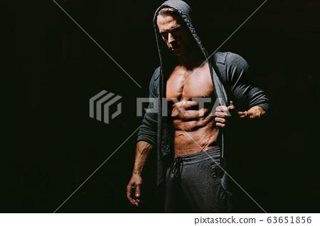 Brutal man wearing hoodie on naked body. 63651856