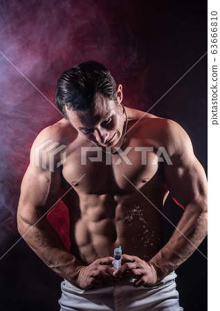 Bodybuilder holding big syringe with injection. concept of steroid in the sport and addiction  63666810