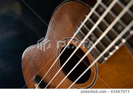 Hawaii ukulele guitar isolated against black background with smoke 63667073
