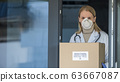 Portrait of a doctor with a box of protective medical masks. 63667087