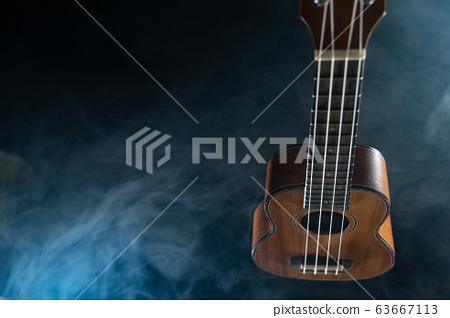 Hawaii ukulele guitar isolated against black background with smoke 63667113