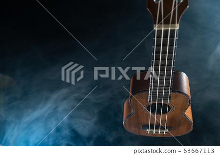 Hawaii ukulele guitar isolated against black background with smoke 63667113