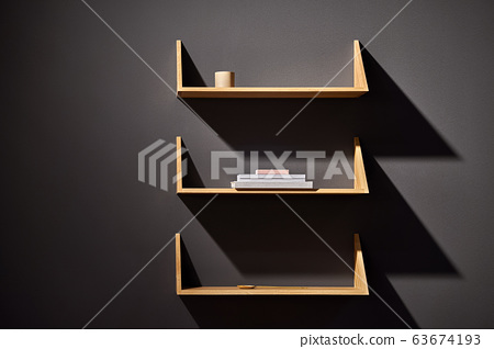 Luminous interior with dark wall and wooden shelves 63674193