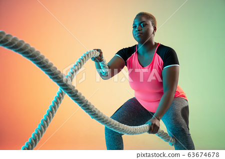Young african-american plus size female model's training on gradient background 63674678