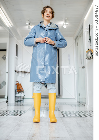 Woman wearing yellow boots and raincoat at the hallway 63684627